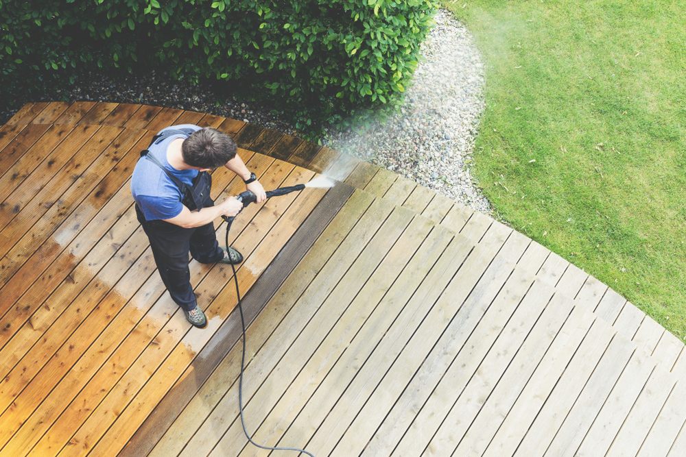 man pressure washes his deck