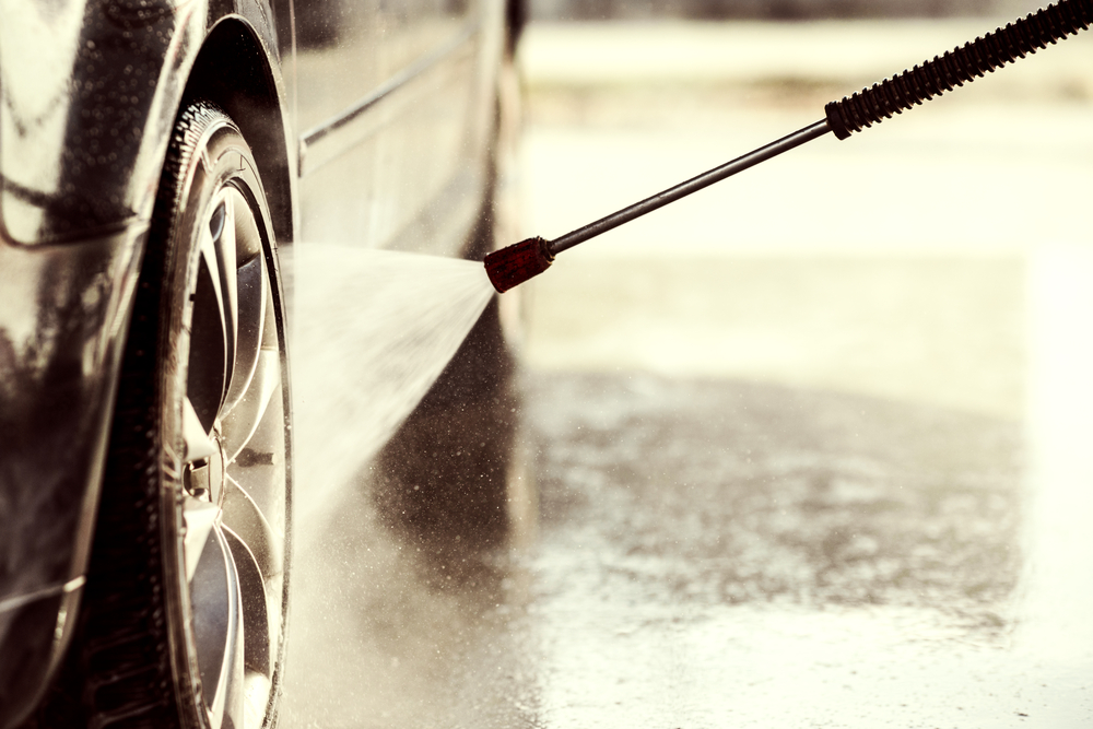 cleaning the tires of a car with a pressure washer