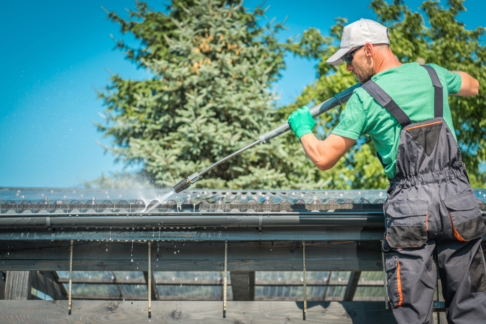 worker learns how to pressure wash gutters on a home
